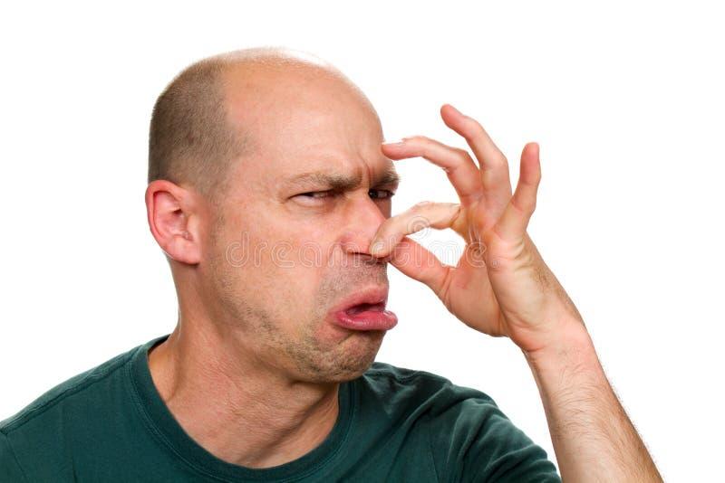 Hållande näsa för man arkivbild