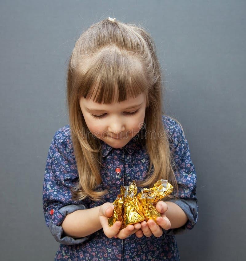 Hållande näve för härlig liten flicka med sötsaker royaltyfria foton