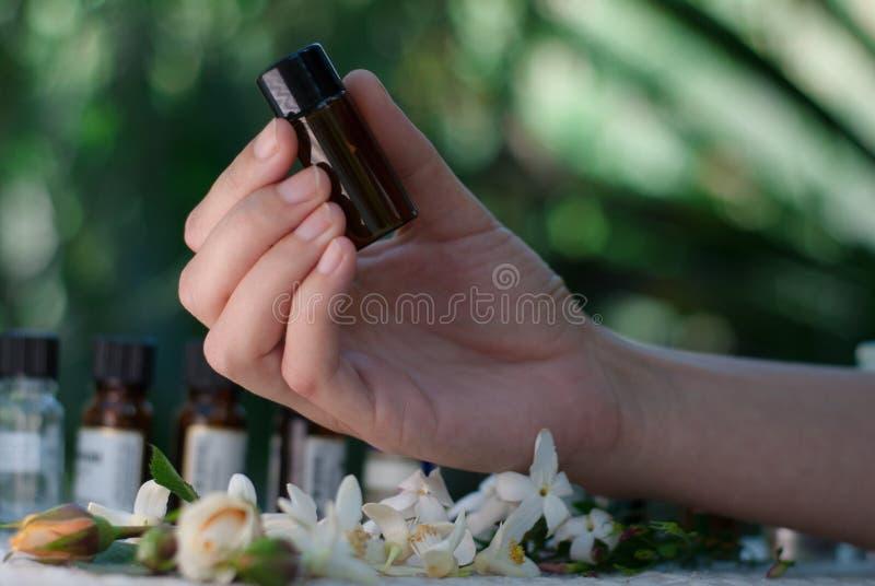 Hållande nödvändig olje- flaska fotografering för bildbyråer