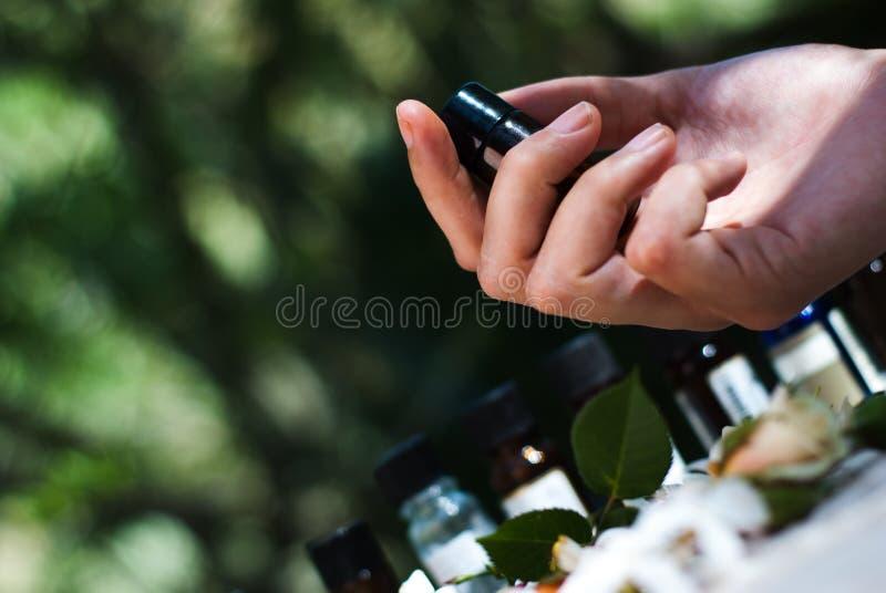 Hållande nödvändig olje- flaska royaltyfri bild