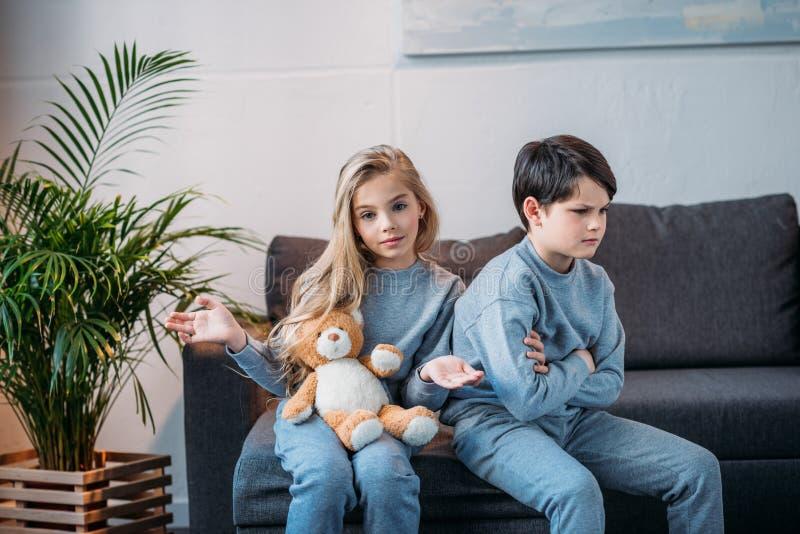 Hållande nallebjörn för flicka medan kränkt pojkesammanträde på soffan hemma royaltyfria bilder