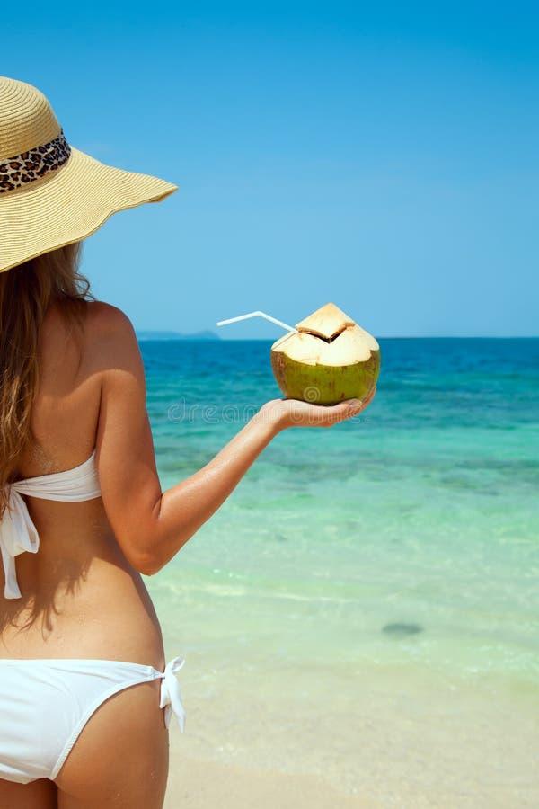 Hållande ny kokosnöt för kvinna på den tropiska stranden fotografering för bildbyråer