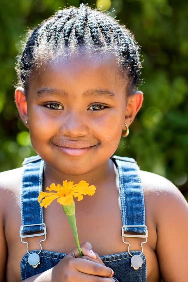 Hållande orange blomma för gullig afrikansk flicka utomhus arkivbilder