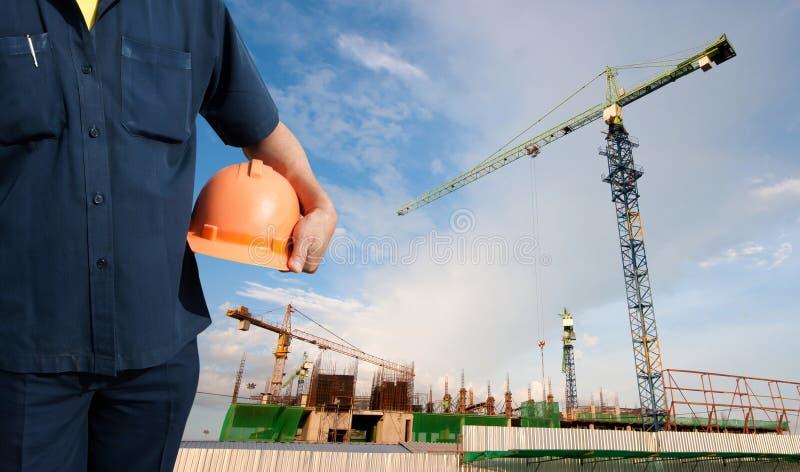 Hållande orange hjälm för tekniker för arbetarsäkerhet royaltyfria foton
