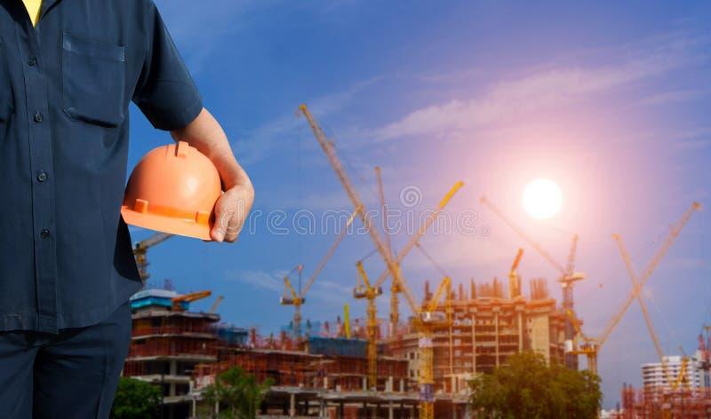 Hållande orange hjälm för tekniker för arbetarsäkerhet arkivfoto