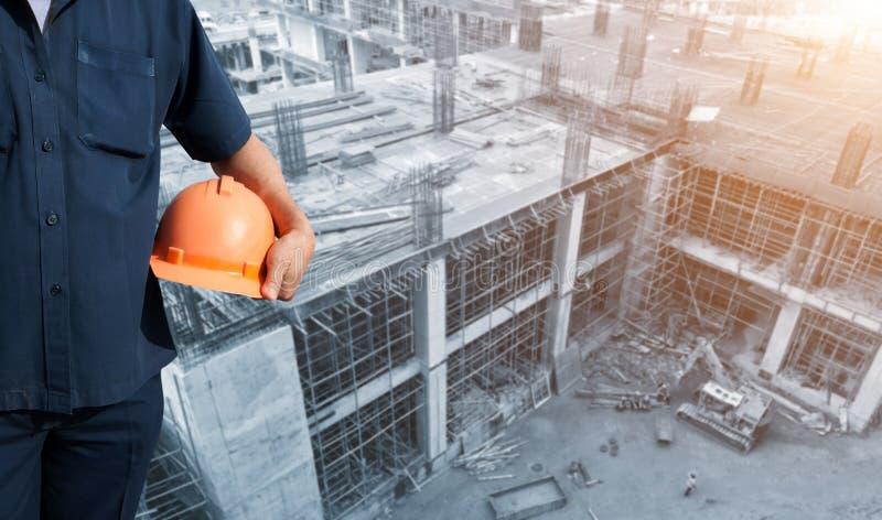 Hållande orange hjälm för tekniker på kontorsbyggnadkonstruktion royaltyfri fotografi