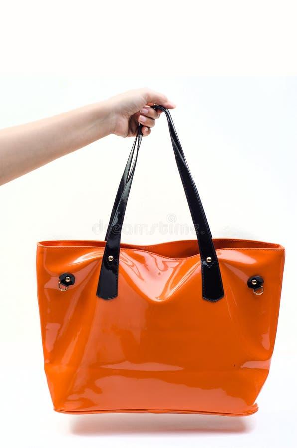 Hållande orange kvinnapåse för hand arkivfoto