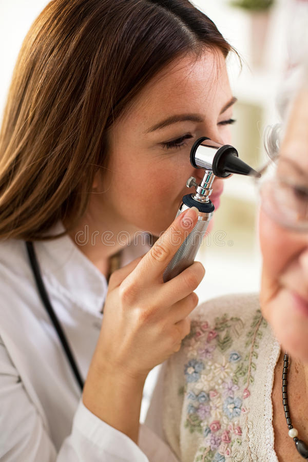 Hållande otoscope för doktor och undersökande öra av den höga kvinnan royaltyfria foton