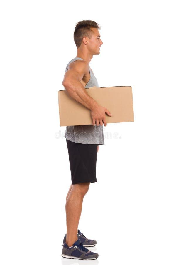 Hållande packe för muskulös man under hans arm arkivfoto