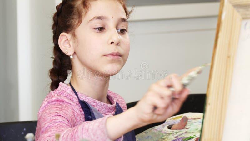 Hållande pallette för nätt liten flicka som målar en bild arkivbild