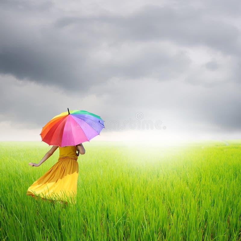 Hållande paraply för härlig kvinna i fält för grönt gräs och rainclouds royaltyfri fotografi