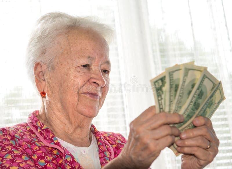 Hållande pengar för gammal kvinna i händer fotografering för bildbyråer