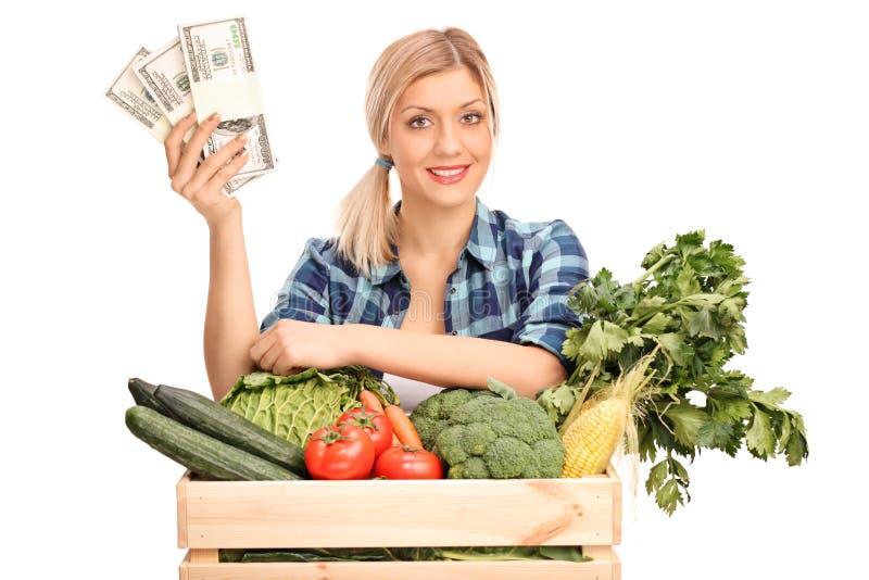 Hållande pengar för kvinnlig jordbruks- arbetare royaltyfri fotografi