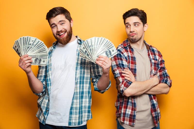 Hållande pengar för lycklig skäggig man och se kameran royaltyfri bild