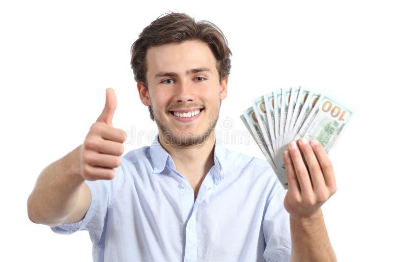 Hållande pengar för ung man med tummar upp arkivfoton