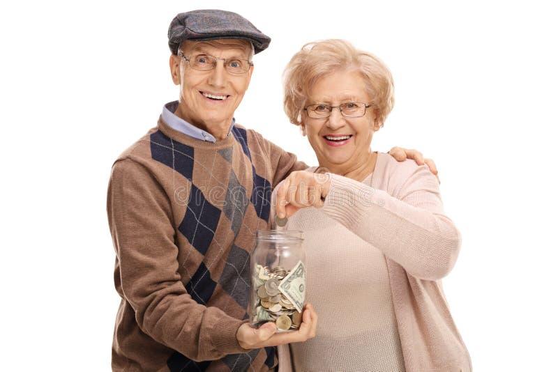 Hållande pengarkrus för äldre man med den äldre kvinnan som sätter myntet royaltyfria bilder