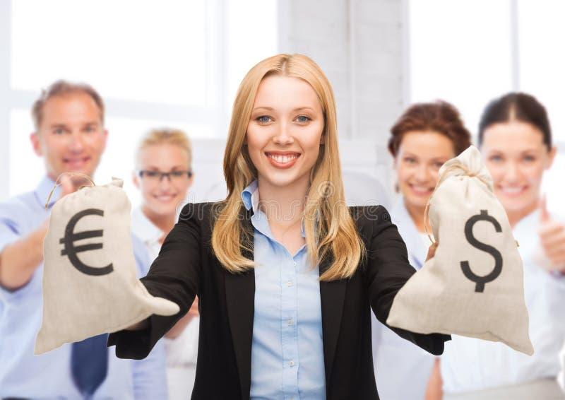 Hållande pengarpåsar för affärskvinna med dollar royaltyfria bilder
