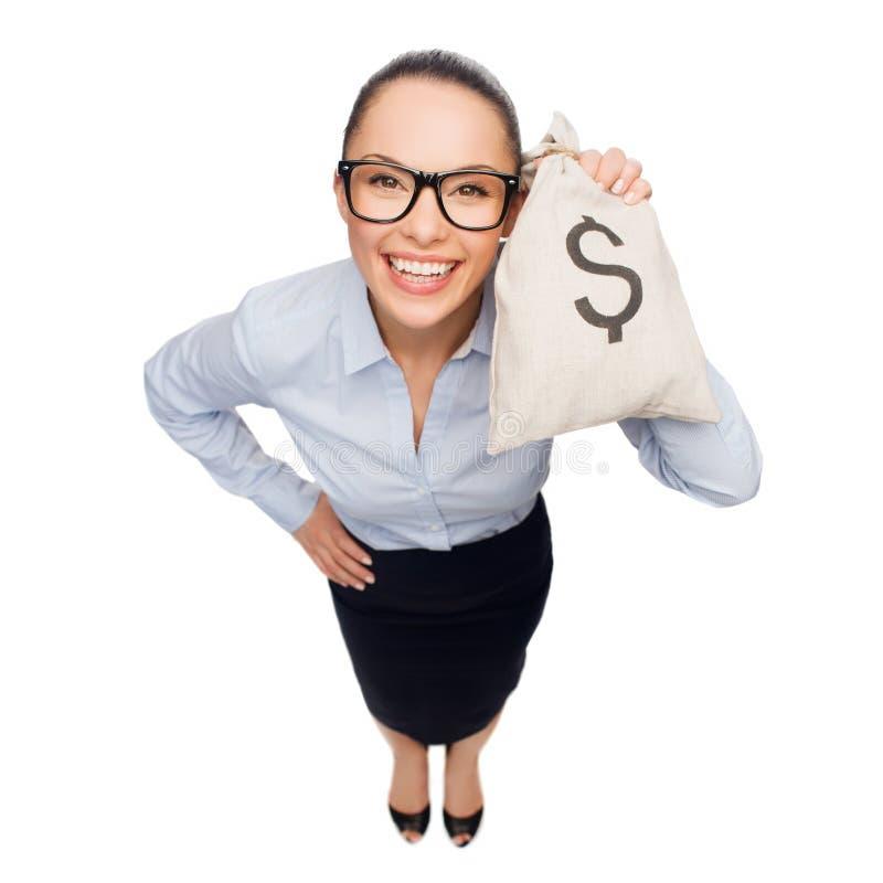Hållande pengarpåse för lycklig affärskvinna med dollaren royaltyfria bilder