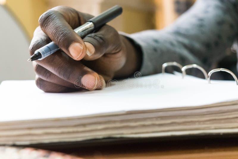 Hållande penna för afrikansk man i handen som ska skrivas på tom vitbok royaltyfria bilder
