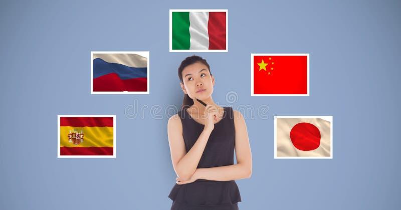 Hållande penna för härlig kvinna och tänka, medan stå vid flaggor mot blå bakgrund arkivfoto