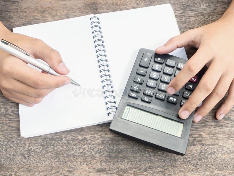 Hållande penna för hand med notepaden och räknemaskinen arkivfoton