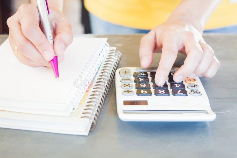 Hållande penna för hand och trängande räknemaskinknappar arkivbilder