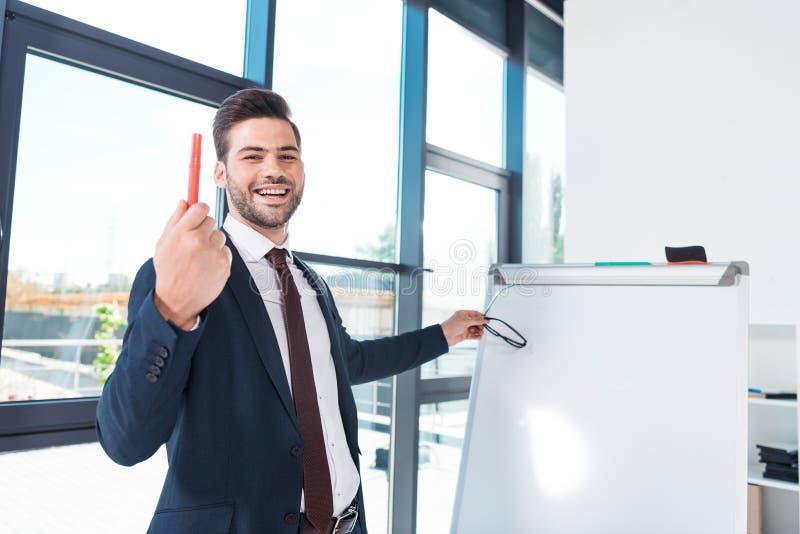 hållande penna för stilig ung affärsman och le på kameran, medan stå near whiteboard royaltyfri bild