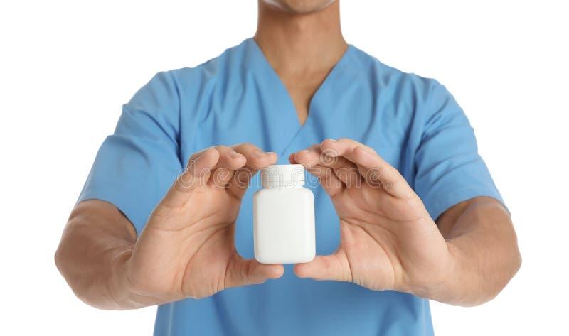 Hållande pillerflaska för manlig doktor på vit bakgrund, closeup med utrymme för text royaltyfri fotografi