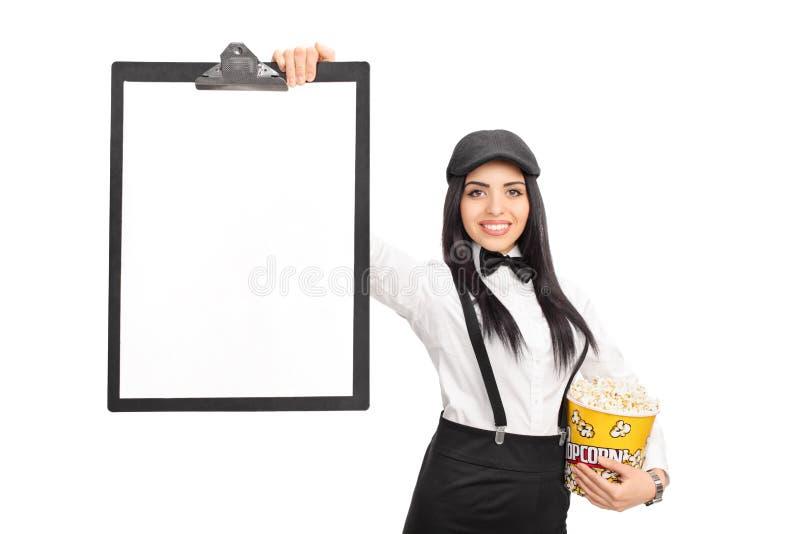 Hållande popcorn för ung kvinna och en skrivplatta royaltyfria bilder