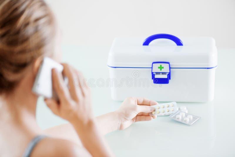 Hållande preventivpillerar för kvinna i blåsapacke och kalla för att manipulera royaltyfria bilder
