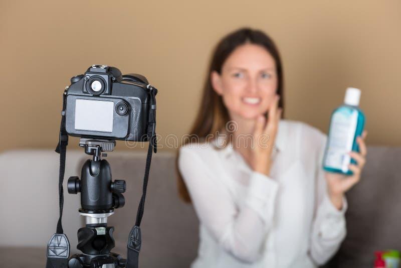 Hållande produktinspelning för kvinnlig Blogger som är video med kameran arkivfoto