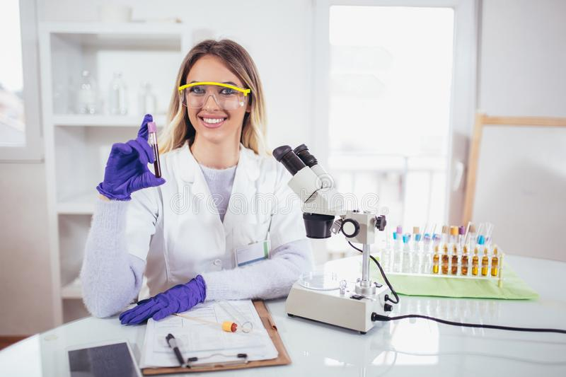 Hållande provrör för ung kvinnlig forskare med blodprövkopian royaltyfria bilder