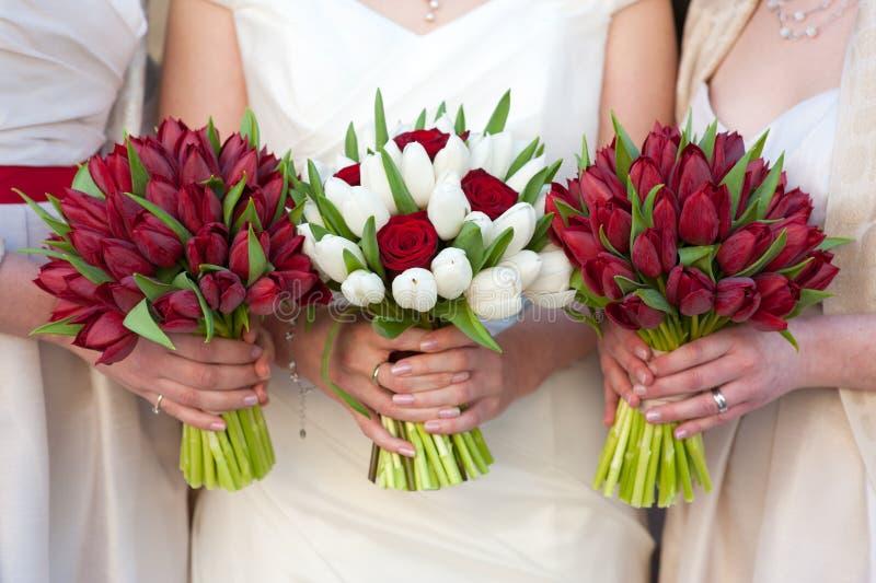 Röda och för vittulpan- och robröllop buketter arkivfoton