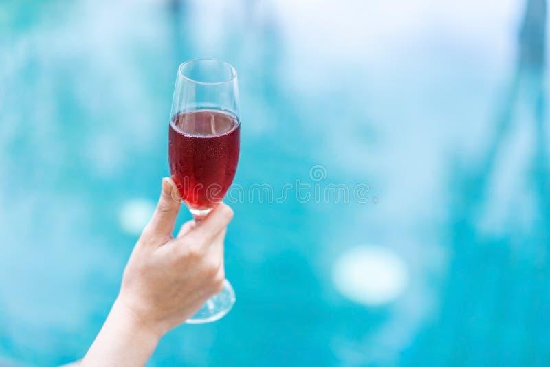 Hållande rött vinexponeringsglas för hand i pöl arkivfoton