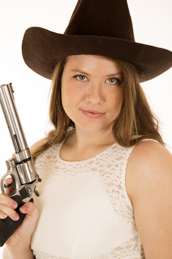 Hållande revolver för cowgirl med en flin på hennes framsida royaltyfria bilder