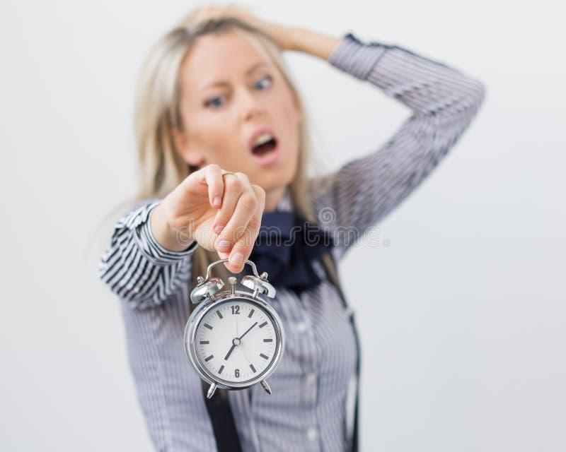 Hållande ringklocka för stressad och frustrerad kvinna arkivbild