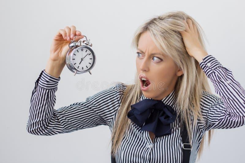 Hållande ringklocka för stressad och frustrerad kvinna arkivfoto