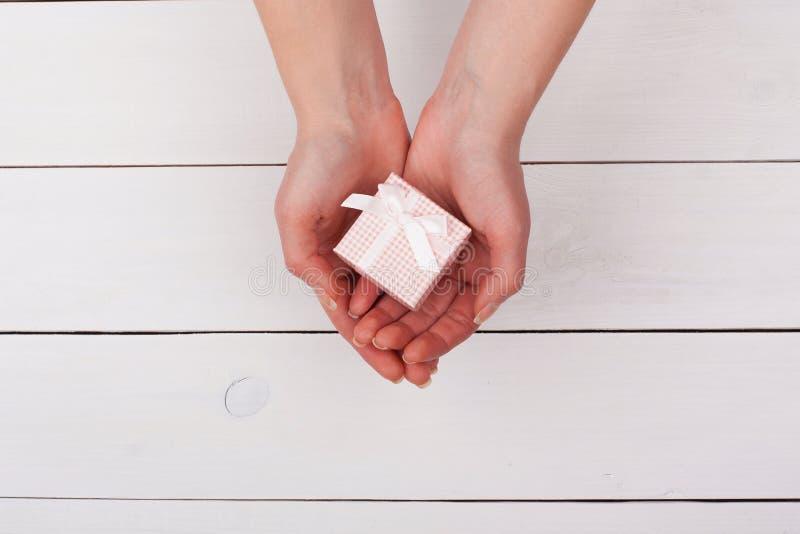 Hållande rosa gåva för kvinnlig hand i händer på en vit trätabell fotografering för bildbyråer