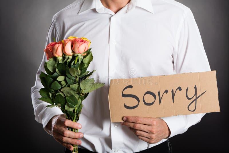 Hållande rosor för man och ledset skriftligt för text på papp royaltyfri bild