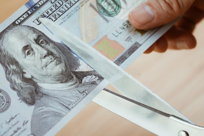 Hållande sax för kvinnahand som klipper US dollarsedlar, snittknopp arkivbilder
