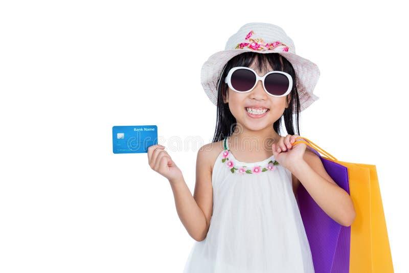 Hållande shoppingpåsar för asiatisk kinesisk liten flicka arkivbilder