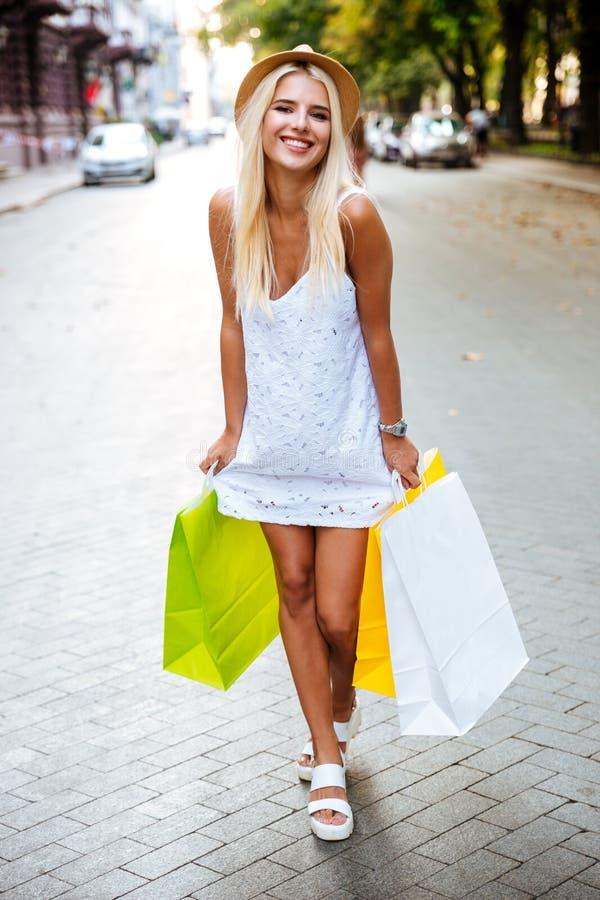 Hållande shoppingpåsar för gladlynt kvinna och gå på gatan royaltyfri bild