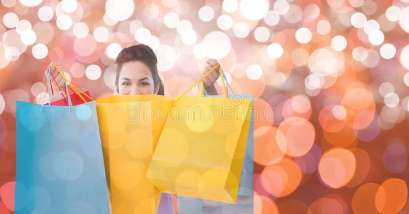 Hållande shoppingpåsar för kvinna över bokeh royaltyfria foton