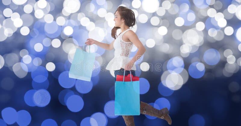 Hållande shoppingpåsar för kvinna, medan gå mot bokeh arkivbilder