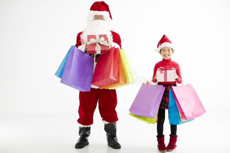 hållande shoppingpåsar för liten flicka och Santa Claus royaltyfri fotografi