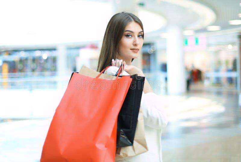 Hållande shoppingpåsar för lycklig kvinna och le på gallerian royaltyfria bilder