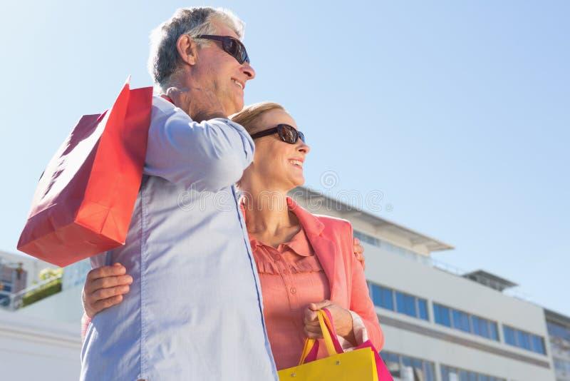 Hållande shoppingpåsar för lyckliga höga par royaltyfria foton