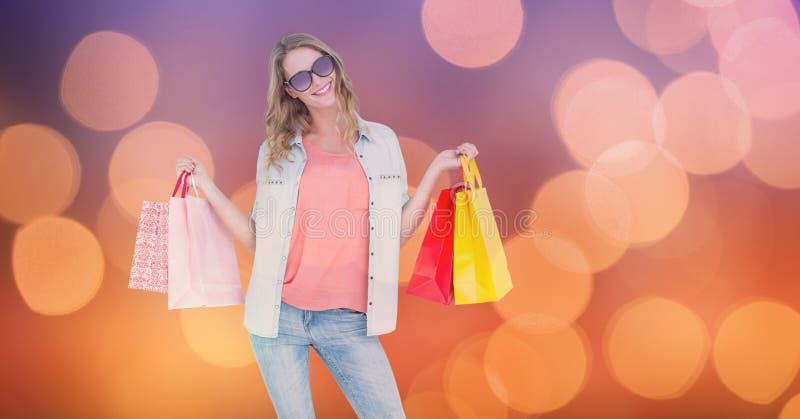 Hållande shoppingpåsar för trendig kvinna över bokeh royaltyfri bild