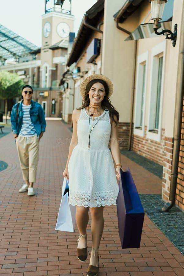 Hållande shoppingpåsar för ung stilfull flicka, medan gå på gatan arkivbild