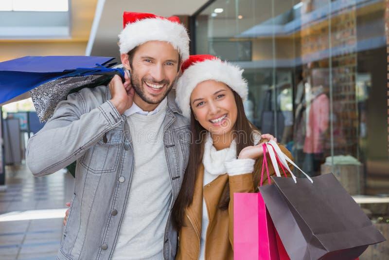 Hållande shoppingpåsar för unga lyckliga par med julhattar på deras hattar arkivfoto
